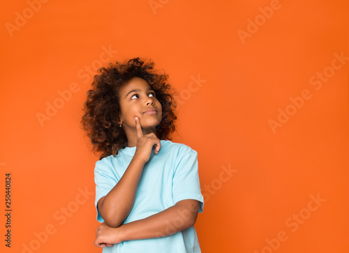 Photo  Little daydreamer. Girl holding finger on chin and looking away