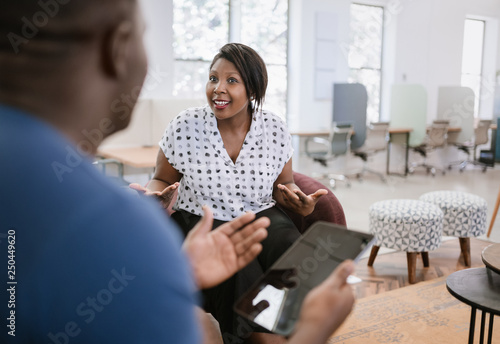 Photo Beautiful black african business woman sitting talking to a man during a meeting, both using expressive hand gestures and the man is holding a digital tablet