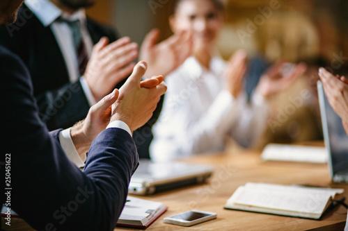 Fototapeta Businessmen are clapping hands on a meeting obraz na płótnie