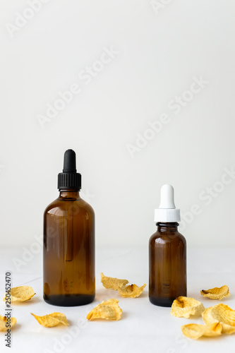 Fotografie, Obraz  Skincare product glass brown serum dropper bottle mockup sample styling with dried yellow roses on white fabric texture table top background with empty copy space