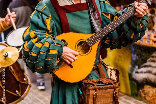 Foto Medieval troubadour playing an antique guitar.