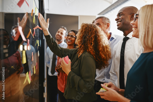Fototapety, obrazy: Office colleagues brainstorming with sticky notes on a glass wal