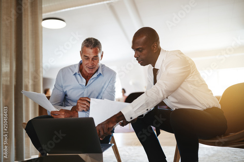 Fototapety, obrazy: Diverse businessmen discussing work on a laptop in an office