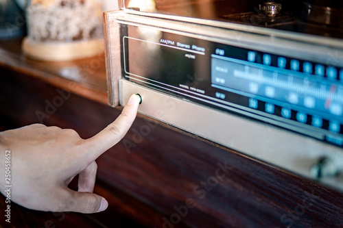 Papel de parede Male hand turning on retro radio by pressing power button