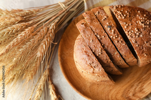 Plate with tasty bread and wheat ears on light table
