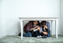 Family Under Table During Earthquake Indoors
