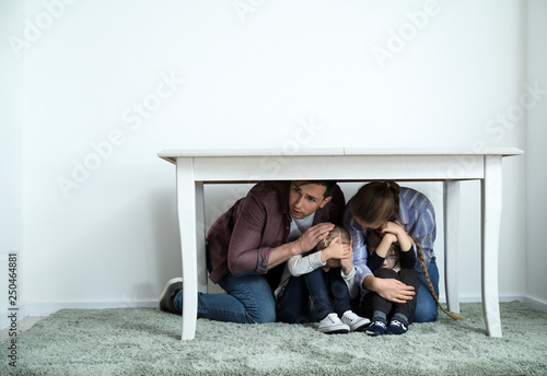 Family under table during earthquake indoors Fototapet