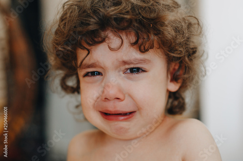 portrait of beautiful crying kinky little boy close up Fotobehang