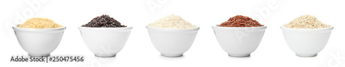 Set of bowls with different uncooked rices on white background