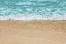 Beautiful Blue Wave With Sea Foam On Sandy Beach