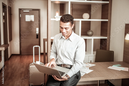 Fotografija  Dark-haired businessman using his laptop while finishing report