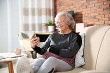 Elderly Woman Using Smartphone On Sofa In Living Room