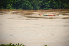 A Long-tailed Boat With Full Passengers Is Running Upstream Against The River Tide Along Muddy Of Mekong River At Amphoe Khong Chiam, The Easternmost District Of Ubon Ratchathani Province Of Thailand.