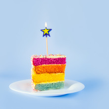 Slice Of Rainbow Cake With Birning Candle In The Shape Of Star On White Round Plate Isolated On Blue Background. Happy Bithday, Party Concept. Square Card. Selective Focus. Copy Space.