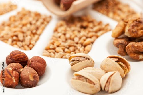Fotografia  Nuts pistachios and grains on white