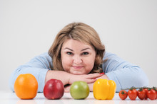Young Lush Fat Woman In Casual Blue Clothes On A White Background At The Table, In Front Of Her In A Row Laid Out Vegetables And Fruits. Diet And Proper Nutrition.