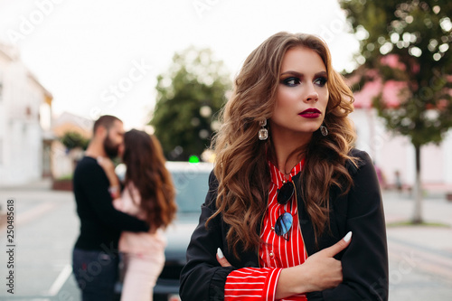 Photo Portrait of gorgeous caucasian woman in stylish elegant clothes and make up looking away with crossed arms against kissing couple in the street