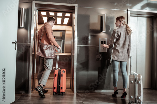 Fotografía  Dark-haired husband entering elevator while going to airport