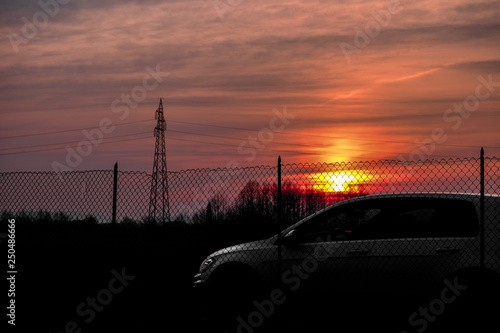 фотография VICENZA, ITALY - January 28, 2019: White hatchback car VW Golf park behind a metal net with the sunshine in a background