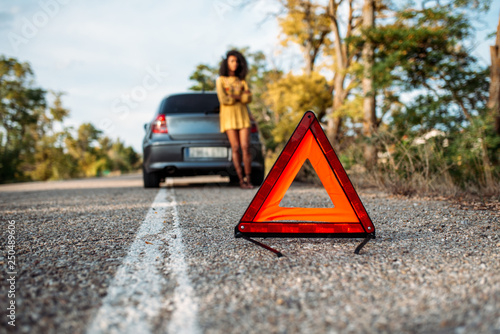 Fotografiet Woman with broken car and triangle