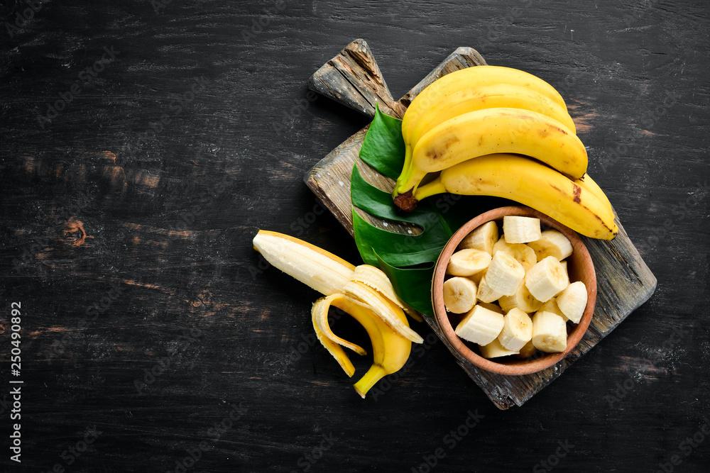 Fotografie, Obraz Bananas on a black wooden surface