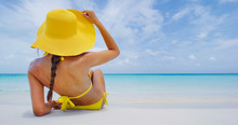 Woman On Beach Vacation Lying In Sand With Beach Hat Sunbathing By Perfect Turquoise Ocean. Elegant Young Adult On Woman For Tropical Travel Luxury Holidays.