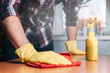 The man in yellow gloves wash the table. The concept of cleaning