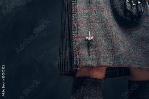 Obraz na płótnie Close-up photo of a traditional Scottish costume against a dark textured wall