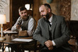 Two bearded men wearing old fashioned suits talking or discuss something in the restaurant