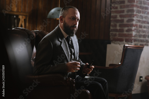 Fotografie, Obraz  Portrait of serious bearded man with pipe holding glass of whiskey wearing suit