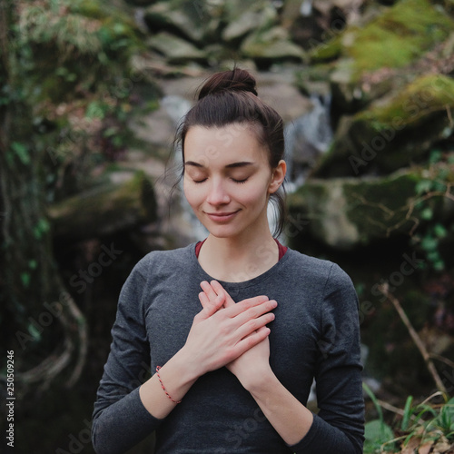 Photo  Young woman practicing breathing yoga pranayama outdoors in moss forest on background of waterfall