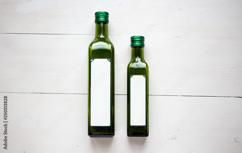 Fototapety, obrazy: Green bottle for olive oil with white blank sticker for your teat of design. Flat lay, top view with white wooden rustic background. Mock up for product illustration.