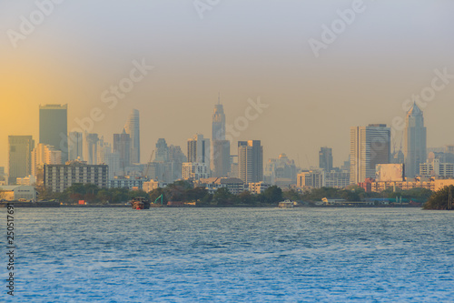 Recess Fitting Dubai Chao Phraya river during sunset with high-rise condominium in blue and yellow sky background. Riverfront view of real estate development, Bangkok, Thailand.