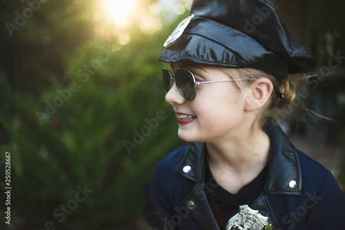 Fotomural Close-up of smiling girl in police costume wearing sunglasses while standing aga