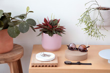 High Angle View Of Personal Accessories With Plants And Keys Arranged On Wooden Table Against Wall At Home