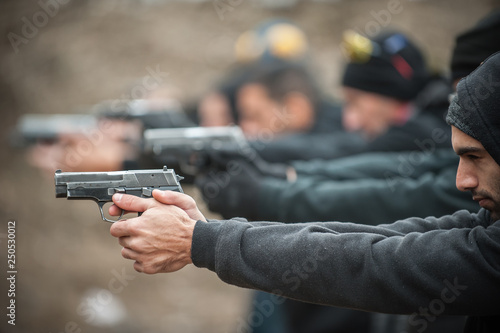 Fotografia Group of civilian practice gun shooting on outdoor shooting range