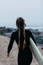 Rear View Of Woman With Braided Hair Carrying Surfboard While Walking On Beach