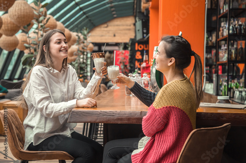 Two happy women are sitting in a cafe, drinking milkshakes, - 250531039