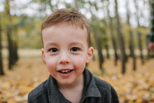 Close-up Portrait Of Cute Smiling Boy Standing In Forest During Autumn