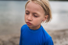 Close Up Of Boy With Eyes Closed Standing In Field