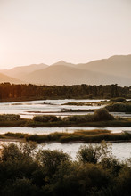 Scenic View Of River And Silhouette Mountains Against Clear Sky During Sunset