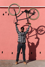 Young Man Wearing Sunglasses Lifting Bicycle Near Wall