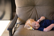 Boy Sleeping With Milk Bottle On Couch At Home