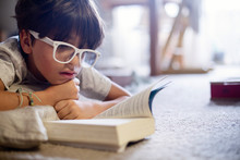 Boy Wearing Eyeglasses Reading Book While Lying On Carpet At Home