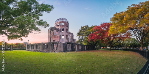 Fotografie, Tablou  The Atomic Bomb Dome Panorama in Hiroshima and the surounding garden in autumn at sunset on the side of Motoyasu River in Japan, with the Peace Memorial Park on the left in the background
