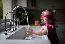 Portrait Of Girl In Superhero Costume Washing Hands In Kitchen Sink