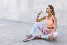 Tired Woman In Sportswear Drinking Water From Bottle After Workout
