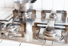Closeup Of Old Rusty Vintage Gas Stove Top With Tiled Outdated White Countertop And Stainless Steel Pot In Retro Kitchen