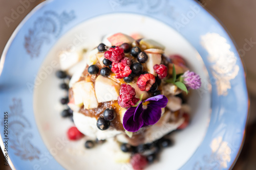 Fototapeta Flat top view of homemade raw vegan ice cream and fresh fruit berries from garden on plate with date syrup topping and purple pansy edible flower obraz