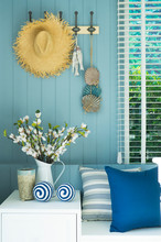 Straw Hat Hanging On Blue Wall